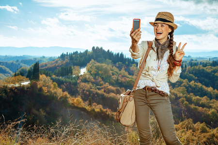 happy fit tourist woman in hiking gear with bag taking selfie with phone and showing victory gesture in the front of scenery of summer Tuscany ,Italy. 版權商用圖片 - 119094360
