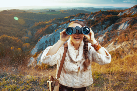 smiling active woman hiker in hiking clothes with bag on summer Tuscany trail looking in camera through binoculars. 版權商用圖片