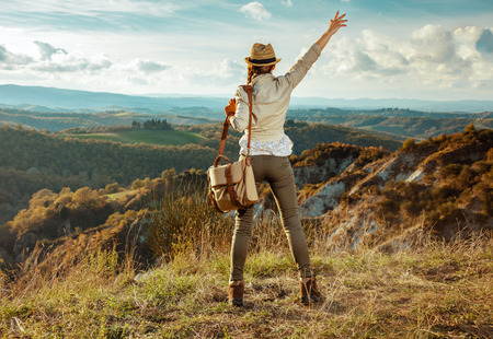 Seen from behind active traveller woman in hiking gear with bag in the front of scenery of summer Tuscany, Italy rejoicing.