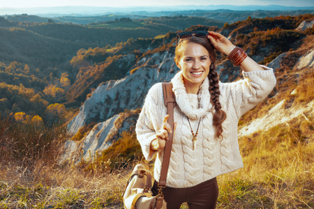 Portrait of happy active solo tourist woman in hiking clothes with bag in the front of scenery of summer Tuscany ,Italy. 版權商用圖片
