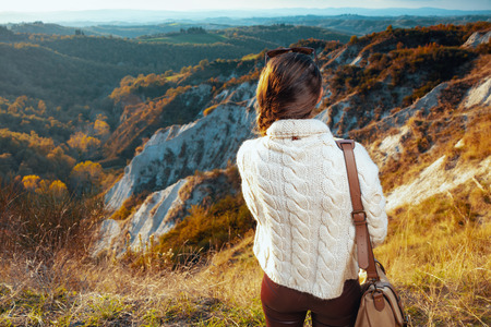Seen from behind active solo tourist woman in hiking gear with bag in the front of scenery of summer Tuscany ,Italy looking into the distance. 版權商用圖片