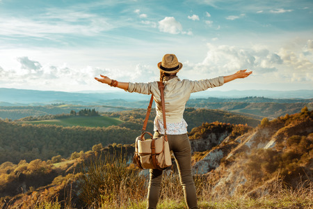 Seen from behind young woman hiker in hiking clothes with bag in the front of scenery of summer Tuscany, Italy rejoicing.
