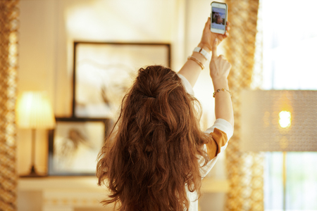 Seen from behind fit housewife with long brunette hair at modern home trying to get better wifi signal on the smartphone.