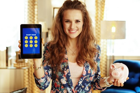 Portrait of smiling fit housewife with long brunette hair showing tablet PC with smart home application and piggy bank in the modern house. 版權商用圖片