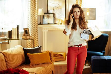 triste jeune femme aux longs cheveux bruns parlant sur un smartphone et essayant de résoudre le problème avec le colis avec un appareil domestique intelligent inadapté dans la maison moderne. Banque d'images