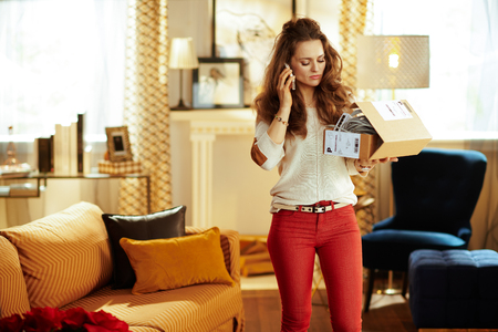 young woman with long brunette hair at modern home and trying to return problematic or unsuitable smart home device.