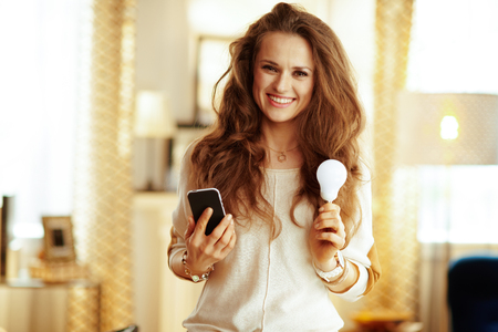 Portrait of happy fit housewife with long brunette hair with smartphone and smart lamp in the modern house. Фото со стока