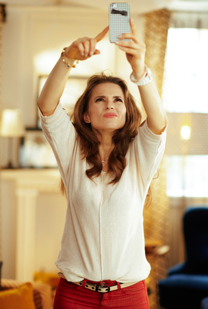 unhappy young housewife with long brunette hair in the modern house trying to get better wifi signal on the smartphone.