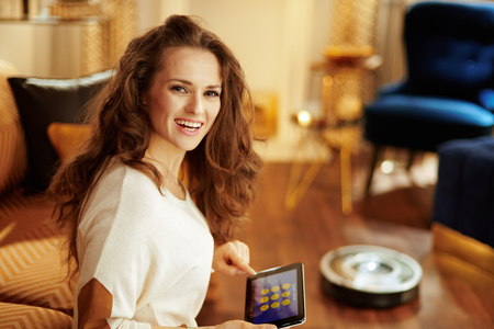 Portrait of smiling fit woman with long brunette hair in the modern house using smart home application on tablet PC and robot vacuum cleaning floor in background.