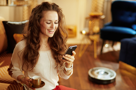 happy young housewife with long brunette hair with coffee cup using smart home app and robot vacuum cleaning floor in background in the modern house.
