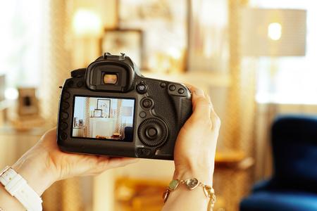 Primer plano de la moderna cámara réflex digital en la mano del fotógrafo de interiores femenino moderno en casa.