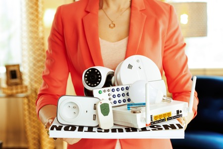 Closeup on smart home devices in hands of modern housewife at home.