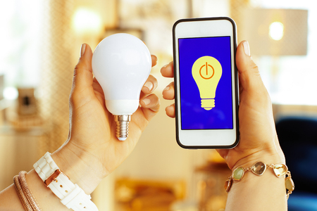 Closeup on smartphone with smart home app and smart lamp in hands of modern housewife at home. Фото со стока
