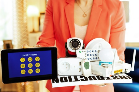 Closeup on smart home devices and tablet PC with smart home application in hands of modern woman in the house.