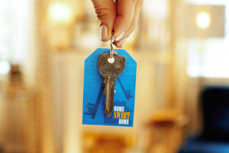 Closeup on door keys with label in hand of modern woman in the house.