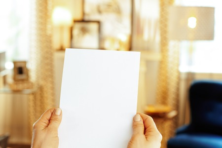 Closeup on blank paper sheet in hand of modern housewife in the house.
