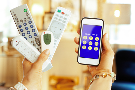 Closeup on remote controls in one hand and smartphone with smart home application in another hand of modern housewife at home. 版權商用圖片