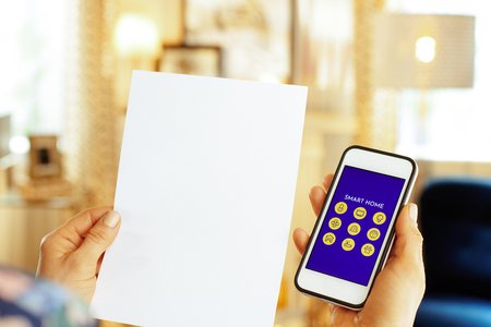 Closeup on blank paper sheet in one hand and smartphone with smart home application in another hand of modern woman in the living room. Standard-Bild - 119650125