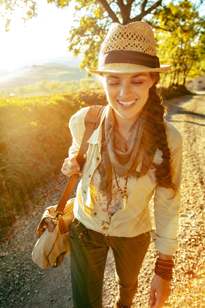 smiling active tourist woman in hiking clothes with bag on summer Tuscany trekking enjoying promenade. Imagens