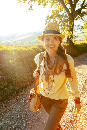 happy healthy traveller woman in hiking gear with bag having walking tour enjoying scenery of summer Tuscany ,Italy.