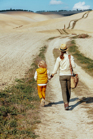 Seen from behind fit mother and child in Tuscany, Italy having walking tour. Banque d'images
