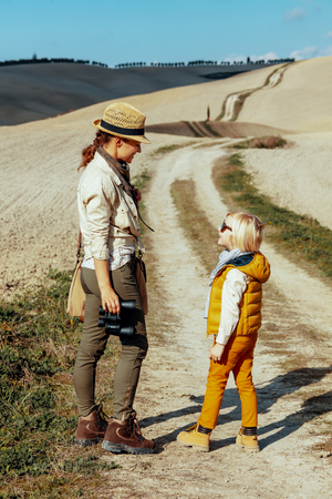 Full length portrait of happy fit mother and daughter with binoculars looking at each other on summer Tuscany trip.