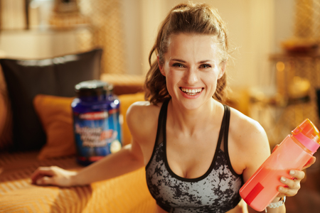 happy healthy sports woman in fitness clothes with shaker with fitness supplements at modern home. Stock Photo