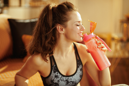 smiling healthy woman in sport clothes drinking from shaker with protein supplements in the modern living room. Stock Photo