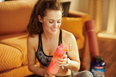 smiling young woman in sport clothes with shaker with fitness supplements in the modern house.