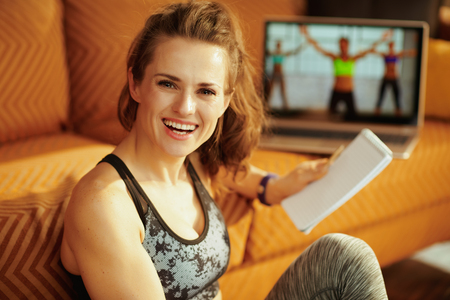 happy active woman in fitness clothes with notepad and pen taking notes while watching fitness tutorial on internet via laptop at modern home. Фото со стока