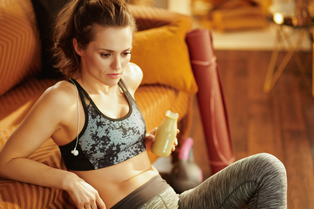 pensive fit sports woman in fitness clothes with bottle of green smoothie in the modern living room. Stock Photo
