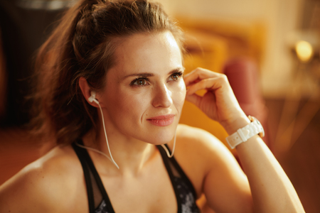 relaxed active sports woman in fitness clothes listening to the music with headphones in the modern living room.