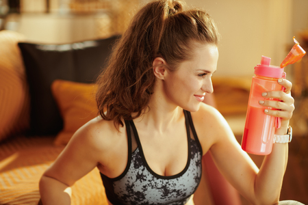 smiling healthy sports woman in sport clothes with shaker with fitness supplements in the modern house.