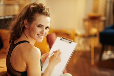 smiling active woman in fitness clothes with clipboard and pen building meal schedule in the modern living room.