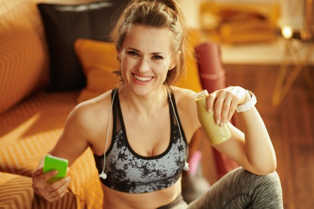 Portrait of happy young woman in sport clothes with headphones and bottle of green smoothie updating a fitness blog via smartphone in the modern house. Фото со стока