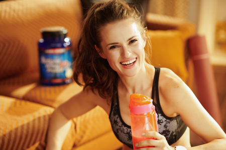 Portrait of smiling healthy sports woman in sport clothes with shaker with protein supplements in the modern house. Stock Photo