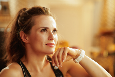 pensive active woman in sport clothes with headphones looking into the distance in the modern house.