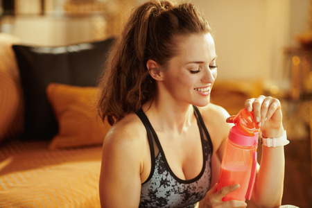 happy active woman in sport clothes with shaker with fitness supplements in the modern house.