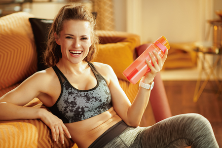 Portrait of smiling young woman in fitness clothes with shaker with fitness supplements in the modern house.