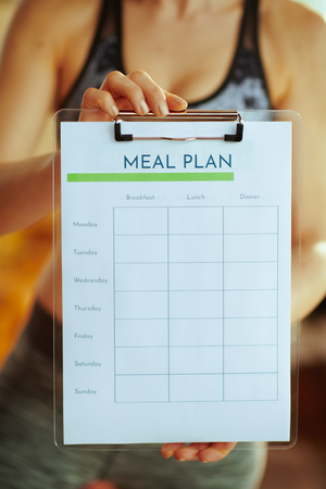 Closeup on fit woman in fitness clothes showing clipboard with meal plan in the modern living room.