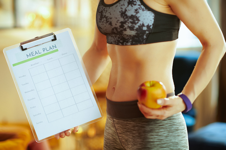 Closeup on active woman in fitness clothes with an apple showing clipboard with meal plan at modern home.