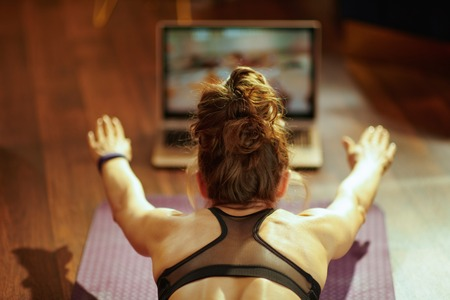 Seen from behind healthy woman in fitness clothes at modern home watching fitness tutorial on internet via laptop while doing exercises on fitness mat.