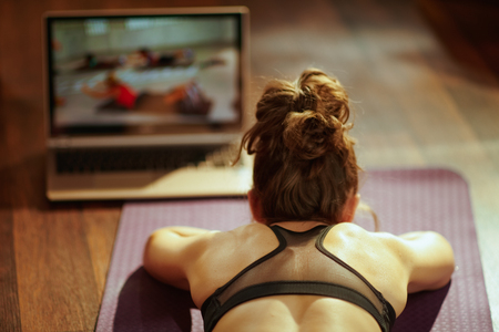 Seen from behind fit sports woman in fitness clothes in the modern living room using online fitness training program in laptop while laying on fitness mat. Фото со стока