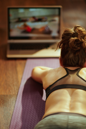 Seen from behind fit sports woman in sport clothes in the modern house watching fitness videos on internet via laptop while laying on fitness mat. Stock Photo