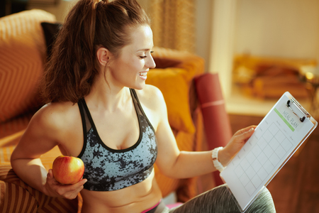smiling fit woman in fitness clothes holding apple and clipboard with meal plan in the modern living room.