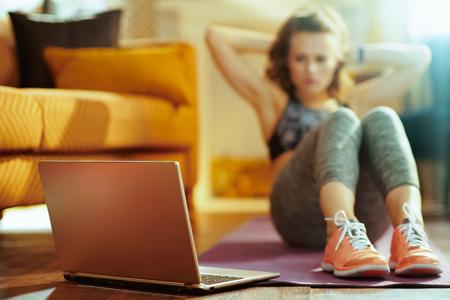 Primer plano en el portátil beige y la mujer en el fondo haciendo abdominales en la estera de fitness mientras ve el tutorial de fitness en internet en la casa moderna.