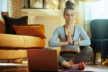 relaxed fit sports woman in fitness clothes in the modern house meditating using online yoga training program in laptop.