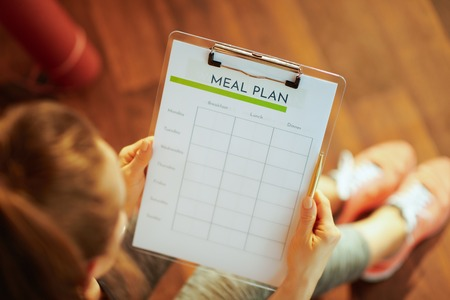 Closeup on active sports woman in fitness clothes with clipboard filling meal plan at modern home. Stock Photo
