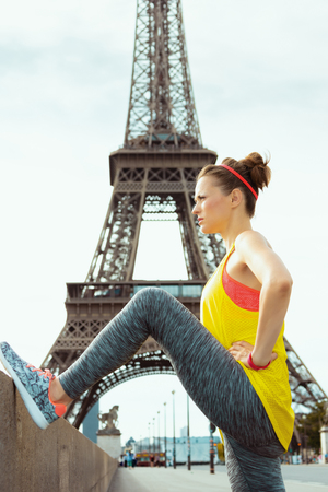 young sports woman in fitness clothes not far from Eiffel tower in Paris, France stretching. Stock Photo