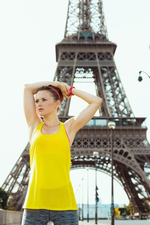 young woman in sport clothes stretching against Eiffel tower in Paris, France.